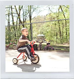 Photograph: A preschool-aged boy rides a tricycle through a playground. (Photograph by Alex Lazara)