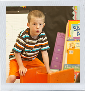 Photograph: A preschool-aged boy stacks plastic chairs in a classroom. (Photograph by Alex Lazara)