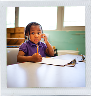Photograph: A preschool-aged girl sits at a table with pencil and paper. (Photograph by Alex Lazara)