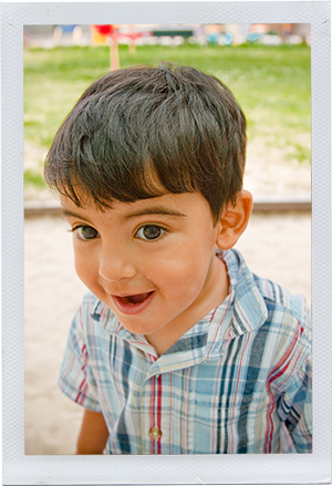 Photograph: A male toddler smiles, distracted by something out of frame. (Photograph by Alex Lazara)