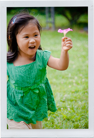 Photograph: A preschool-aged girl runs across a grass field with a pink flower in her hand. (Photograph by Alex Lazara)
