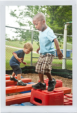 Photograph: Two preschool-aged boys balance themselves on plastic play equipment. (Photograph by Alex Lazara)