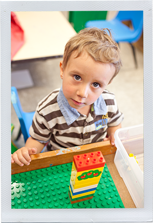 Photograph: A preschool-aged boy looks up from his stack of building blocks. (Photograph by Alex Lazara)
