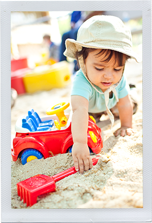Photograph: An toddler reaches for his shovel in a sandbox. (Photograph by Alex Lazara)