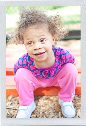 Photograph: A female toddler leans over and smiles at the camera. (Photograph by Alex Lazara)
