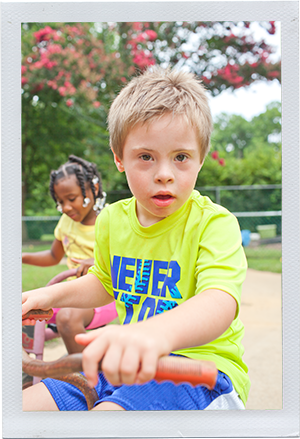 Photograph: A preschool-aged boy looks over the handlebars of his tricycle. (Photograph by Alex Lazara)