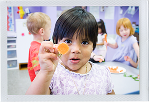 Photograph: A female toddler holds up the end of a carrot during snack time. (Photograph by Alex Lazara)