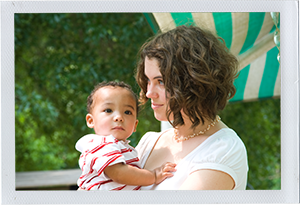 Photograph: A child care professional holds an infant boy outdoors. (Photograph by Alex Lazara)