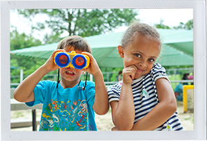 Photograph: A pair of preschool aged friends pose with a pair of toy binoculars. (Photograph by Alex Lazara)