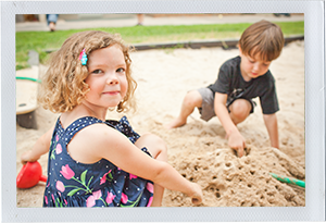 Photograph: Two preschool-aged children poke holes in wet sandbox sand with their fingers. (Photograph by Alex Lazara)
