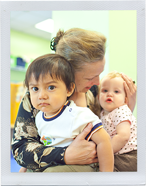 Photograph: A child care professional holds two infants in her lap. (Photograph by Alex Lazara)