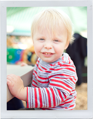 Photograph: A male toddler in a striped shirt smiles at the camera. (Photograph by Alex Lazara)