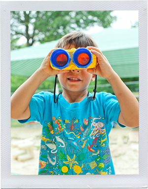 Photograph: A preschool-aged boy looks through a pair of toy binoculars. (Photograph by Alex Lazara)