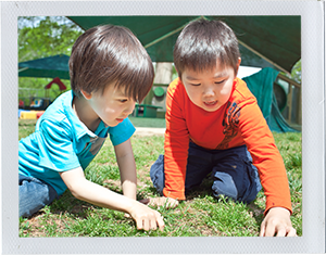 Photograph: A pair of preschool-aged boys examine a grass field up close. (Photograph by Alex Lazara)