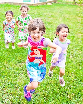 Photograph: Several young children run across a grass field.