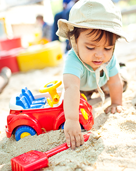 Photograph: A toddler reaches for a shovel in a sandbox.