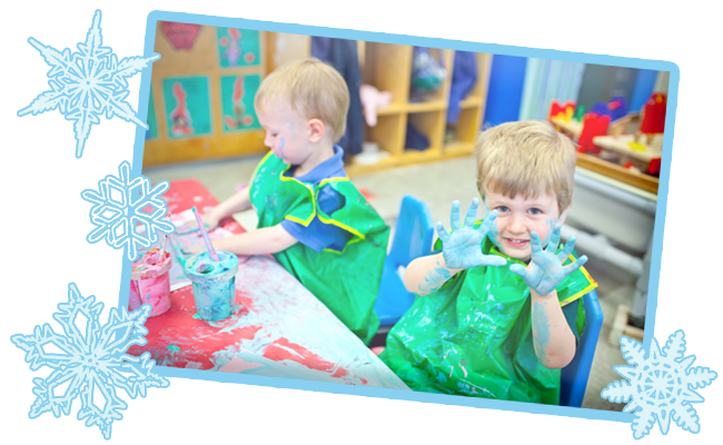 Photograph: Two preschool aged children fingerpaint at a desk in a classroom. One holds up his hands, covered in blue paint. The photograph is ringed by drawn artwork of snowflakes.